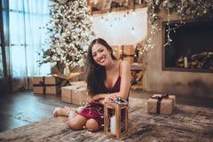 Het jonge mooie Aziatische meisje is zitting van de manier de rode kleding thuis dichtbij Kerstmisboom in comfortabel binnenland  stock afbeeldingen