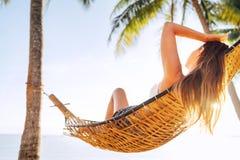 Het jonge mooie blonde longhaired vrouw ontspannen in hangmat onder palmen op het zandstrand stock foto