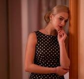 Het jonge mooie blonde met haar dat in een chignon in een stipkleding wordt verzameld bevindt zich bij de deur met een nadenkende royalty-vrije stock fotografie