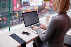 Het jonge mooie blondemeisje gebruikt laptop en telefoon terwijl de werkende reisoortelefoons voor het creëren van artikel voor W stock fotografie