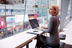 Het jonge mooie blondemeisje gebruikt laptop en telefoon terwijl het werken van reis royalty-vrije stock foto's