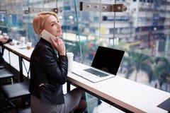 Het jonge mooie blondemeisje gebruikt laptop en telefoon terwijl het werken van reis royalty-vrije stock afbeelding