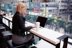Het jonge mooie blondemeisje gebruikt laptop en telefoon terwijl het werken van reis royalty-vrije stock foto