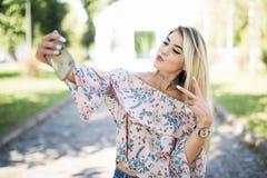 Het jonge mooie blondemeisje ontspannen in park, die een selfie nemen door mobiele telefoon Stock Afbeelding
