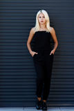 Het jonge mooie blondemeisje stellen op de achtergrond van het stedelijke landschap Sexy dame in een zwarte kleding royalty-vrije stock afbeelding