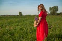 Het jonge mooie blondevrouw smilling met bloemen in aard in de zomer royalty-vrije stock foto