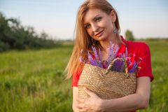 Het jonge mooie blondevrouw smilling met bloemen in aard in de zomer stock foto's