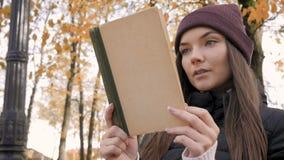 Het jonge mooie boek van de meisjeslezing in de herfstpark stock footage