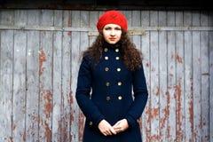 Het jonge mooie brunette in breit baret en een laag Stock Foto's