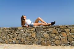 Het jonge mooie brunette in de borrels van Jean geniet van Stock Foto's