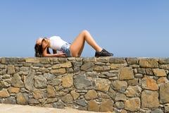 Het jonge mooie brunette in de borrels van Jean geniet van Stock Foto