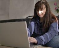 Het jonge mooie brunette glimlacht terwijl het typen op laptop stock afbeelding