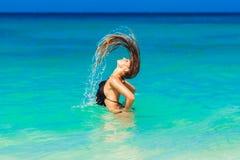 Het jonge mooie brunette met lang haar in zwart zwempak geniet van swi royalty-vrije stock afbeeldingen