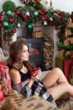 Het jonge mooie brunette op Kerstmisvooravond zit dichtbij een open haard en drinkt thee van een rode mok Stock Foto