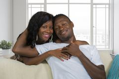 Het jonge mooie en gelukkige zwarte Afrikaanse Amerikaanse paar in liefde ontspande bij modern huiswoonkamer geknuffelsnoepje op  stock fotografie