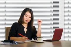 Het jonge mooie en succesvolle Aziatische Chinese bedrijfsvrouw werken zeker bij het moderne bureau van de bureaucomputer in wijf stock foto