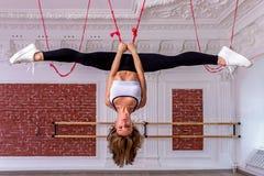 Het jonge mooie flexibele meisje in witte gewassen hoogste en zwarte beenkappen hangt bovenkant - neer in de spleten Het uitrekke stock afbeeldingen