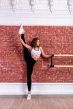 Het jonge mooie flexibele meisje in witte gewassen hoogste en zwarte beenkappen stelt in dansstudio Het uitrekken zich en het the royalty-vrije stock afbeeldingen