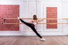 Het jonge mooie flexibele meisje in witte gewassen hoogste en zwarte beenkappen stelt in dansstudio Het uitrekken zich en het the stock foto's