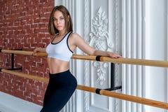 Het jonge mooie flexibele meisje in witte gewassen hoogste en zwarte beenkappen stelt in dansstudio Het uitrekken zich en het the stock foto