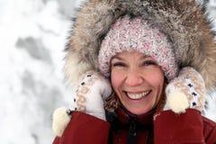 Het jonge mooie glimlachende meisje in roze gebreide hoed met pompon en de witte vuisthandschoenen met patroon in warm jasje van  stock foto