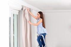 Het jonge mooie gordijn van het vrouwen hangende venster royalty-vrije stock afbeeldingen