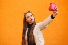 Het jonge mooie hipstermeisje in gele zonnebril maakt selfie door roze onmiddellijke camera op oranje muur Stedelijke stijl Stock Fotografie