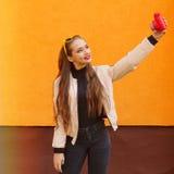 Het jonge mooie hipstermeisje in gele zonnebril maakt selfie door roze onmiddellijke camera op oranje muur Stedelijke stijl Stock Afbeelding