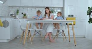 Het jonge mooie mamma in een witte kleding met twee kinderen glimlacht en eet verse burgers in hun keuken stock video