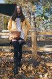 Het jonge mooie meisje bevindt zich dichtbij de houten omheining in stadsdierentuin Stock Foto