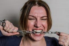 Het jonge mooie meisje bijt de ketting met haar tanden, die het proberen uit voor te stellen stock foto's