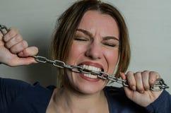 Het jonge mooie meisje bijt de ketting met haar tanden, die het proberen uit voor te stellen stock foto