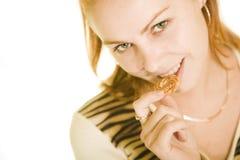 Het jonge mooie meisje bijt een cake Stock Afbeelding