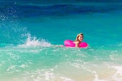 Het jonge mooie meisje in bikini zwemt in een tropische overzees op een rubb stock foto