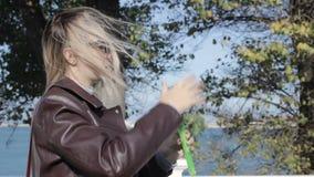Het jonge mooie meisje blaast zeepbels, openlucht stock footage
