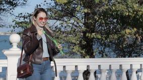 Het jonge mooie meisje blaast zeepbels, openlucht stock video