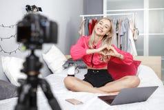 Het jonge mooie meisje blogger gekleed in heldere modieuze kleren wordt gefilmd op de videocamera voor haar blogzitting stock foto