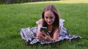 Het jonge mooie meisje die telefoon met behulp van ligt op gras in het park stock videobeelden