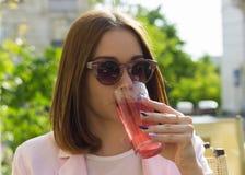 Het jonge mooie meisje drinkt een koude drank, openlucht royalty-vrije stock afbeeldingen