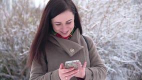 Het jonge, mooie meisje, in een laag, in een de winterpark, schrijft een bericht stock video