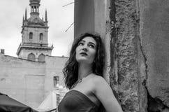 Het jonge mooie meisje in een rode kleding wandelt door de oude straten van de stad van Lviv stock fotografie