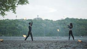 Het jonge mooie meisje en de knappe mens in het zwarte kleren presteren tonen met vlam die zich op riverbank bevinden De vrouw stock video
