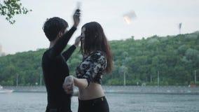 Het jonge mooie meisje en de knappe mens in het zwarte kleren presteren tonen met vlam die zich op riverbank bevinden De vrouw stock footage