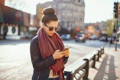 Het jonge mooie meisje gebruikt de telefoon royalty-vrije stock fotografie