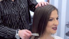 Het jonge mooie meisje glimlacht terwijl kapper het werken met haar haar stock video