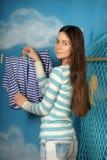 Het jonge mooie meisje hangt kleren Stock Fotografie