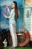 Het jonge mooie meisje hangt kleren Stock Afbeelding