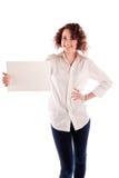 Het jonge mooie meisje houdt een leeg wit teken voor u om in te vullen Stock Afbeelding