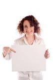 Het jonge mooie meisje houdt een leeg wit teken voor u om in te vullen Stock Foto