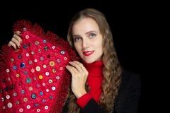 Het jonge mooie meisje houdt rode stof met kleurrijke knopen stock afbeeldingen